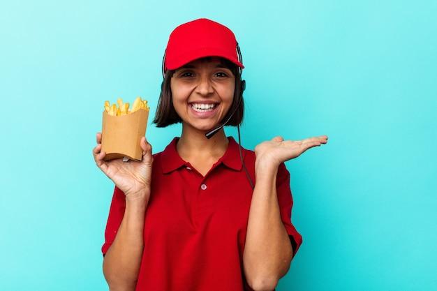 Junge gemischtrassige frau fast-food-restaurantarbeiterin, die pommes auf blauem hintergrund isoliert hält und einen kopienraum auf einer handfläche zeigt und eine andere hand an der taille hält.
