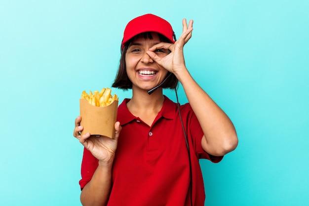 Junge gemischtrassige frau fastfood-restaurantarbeiterin, die pommes auf blauem hintergrund isoliert hält, aufgeregt, die geste auf dem auge zu halten.