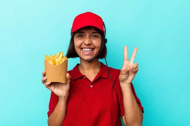 Junge gemischtrassige frau fastfood-restaurantarbeiterin, die pommes auf blauem hintergrund isoliert hält, fröhlich und unbeschwert, die ein friedenssymbol mit den fingern zeigt