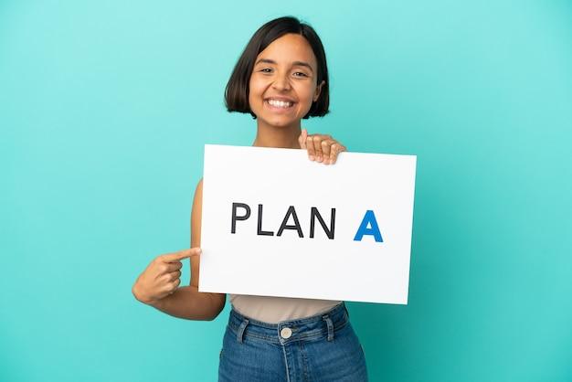 Junge gemischtrassige frau isoliert auf blauem hintergrund, die ein plakat mit der nachricht plan a hält und darauf zeigt