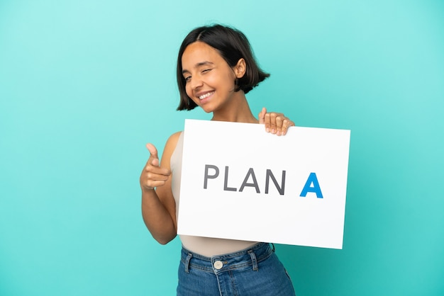 Junge gemischtrassige frau isoliert auf blauem hintergrund, die ein plakat mit der nachricht plan a hält und nach vorne zeigt