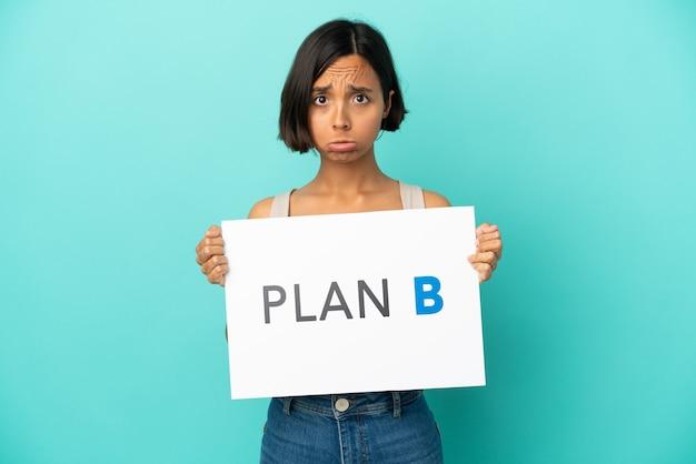 Junge gemischtrassige frau isoliert auf blauem hintergrund, die ein plakat mit der nachricht plan b mit traurigem ausdruck hält