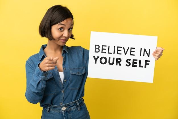 Junge gemischtrassige frau isoliert auf gelbem hintergrund, die ein plakat mit dem text believe in your self hält und nach vorne zeigt