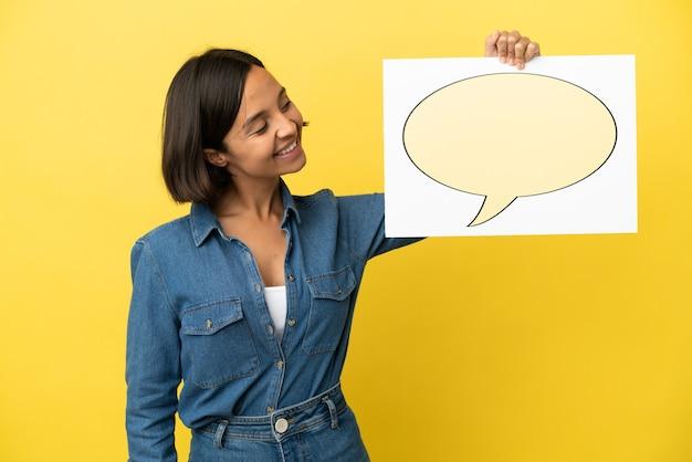 Junge gemischtrassige frau isoliert auf gelbem hintergrund, die ein plakat mit sprechblase-symbol hält Premium Fotos