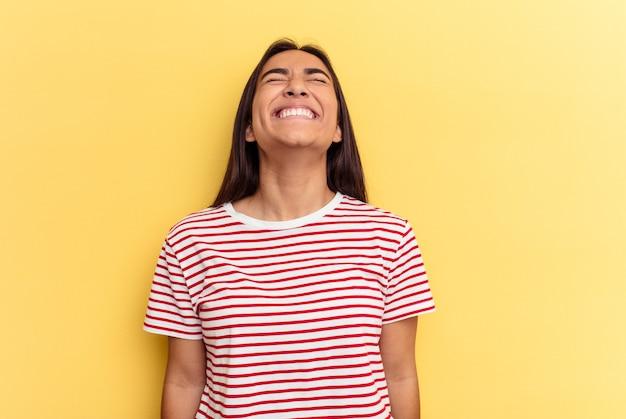 Junge gemischtrassige frau isoliert auf gelbem hintergrund entspannt und glücklich lachend, hals gestreckt, zähne zeigend.