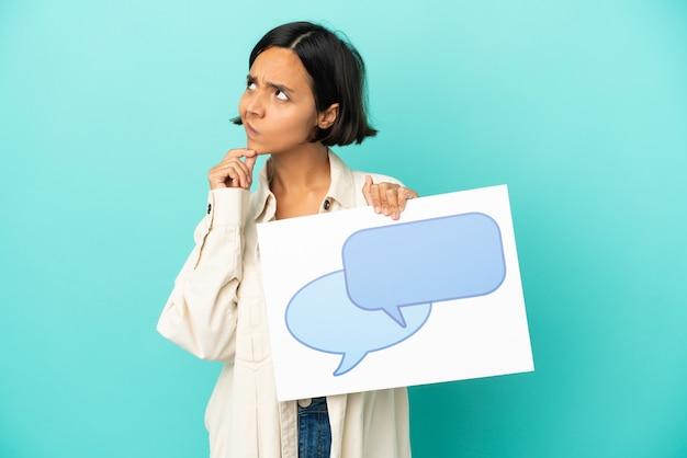 Junge gemischtrassige frau isoliert, die ein plakat mit sprechblasensymbol hält und denkt