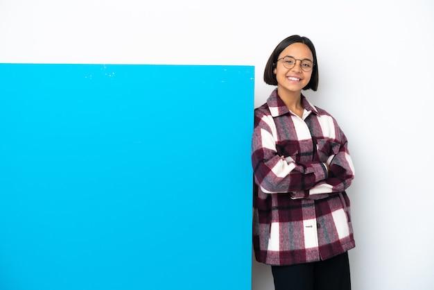Junge gemischtrassige frau mit einem großen blauen plakat isoliert auf weißem hintergrund, das die arme in frontalposition verschränkt hält Premium Fotos