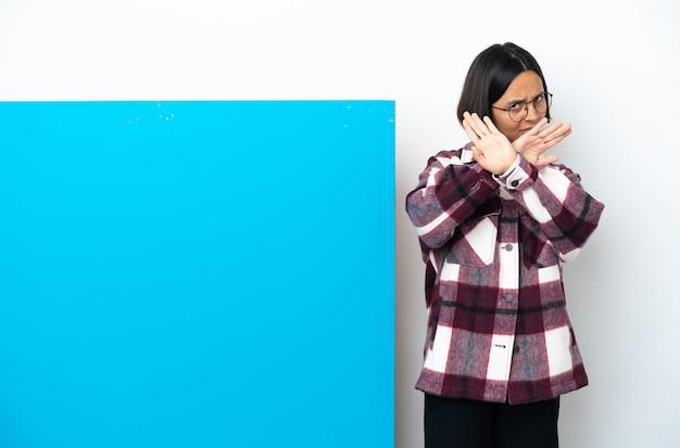 Junge gemischtrassige frau mit einem großen blauen plakat isoliert auf weißem hintergrund, das mit der hand eine stopp-geste macht, um eine handlung zu stoppen