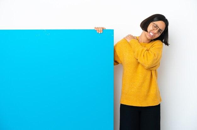 Junge gemischtrassige frau mit einem großen blauen plakat isoliert auf weißem hintergrund, die unter schmerzen in der schulter leidet, weil sie sich bemüht hat