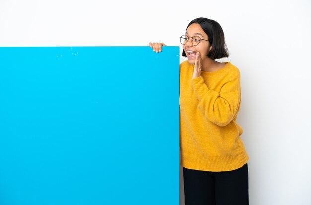 Junge gemischtrassige frau mit einem großen blauen plakat isoliert auf weißem hintergrund schreien mit weit geöffnetem mund zur seite