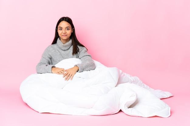 Junge gemischtrassige frau mit pyjama, die auf dem boden in rückenposition sitzt