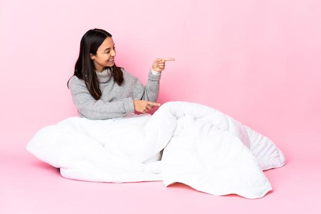 Junge gemischtrassige frau mit pyjama, die auf dem boden sitzt, mit dem finger zur seite zeigt und ein produkt präsentiert