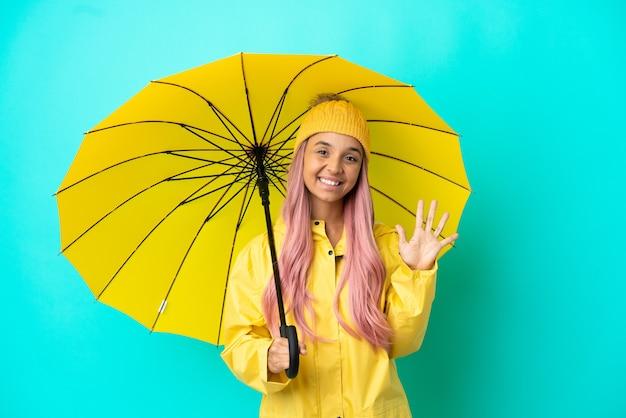 Junge gemischtrassige frau mit regenfestem mantel und regenschirm, die mit den fingern fünf zählt