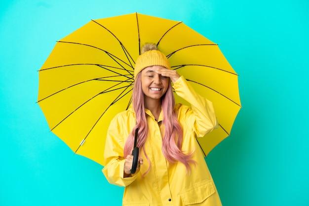 Junge gemischtrassige frau mit regenfestem mantel und regenschirm, die viel lächelt