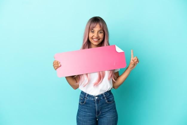 Junge gemischtrassige frau mit rosa haaren auf blauem hintergrund isoliert, die ein leeres plakat hält