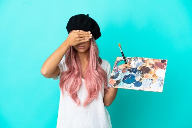 Junge gemischtrassige frau mit rosa haaren, die eine auf blauem hintergrund isolierte palette hält, die die augen mit den händen bedeckt. will etwas nicht sehen