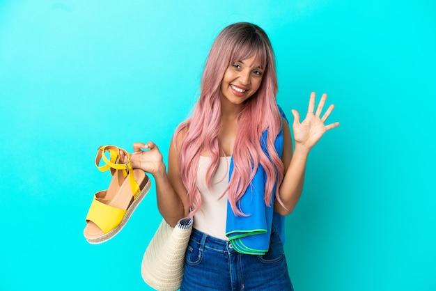 Junge gemischtrassige frau mit rosa haaren, die sommersandalen hält, die auf blauem hintergrund isoliert sind und fünf mit den fingern zählen
