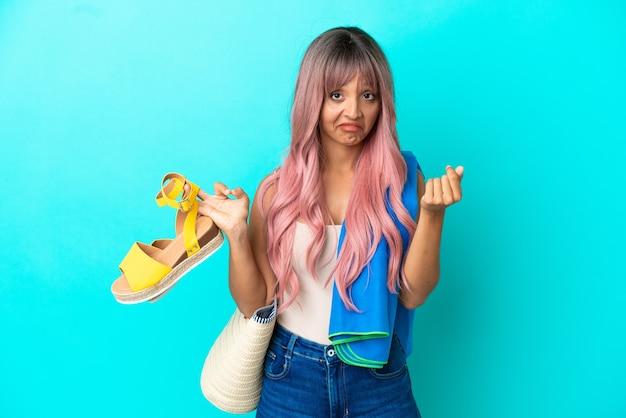 Junge gemischtrassige frau mit rosa haaren, die sommersandalen isoliert auf blauem hintergrund hält und geldgeste macht