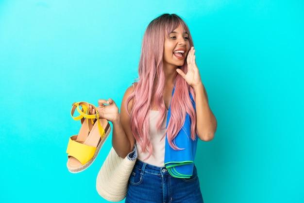 Junge gemischtrassige frau mit rosa haaren, die sommersandalen isoliert auf blauem hintergrund hält und mit weit geöffnetem mund zur seite schreit
