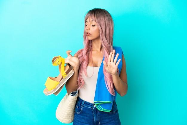 Junge gemischtrassige frau mit rosa haaren, die sommersandalen isoliert auf blauem hintergrund hält und stoppgeste macht und enttäuscht