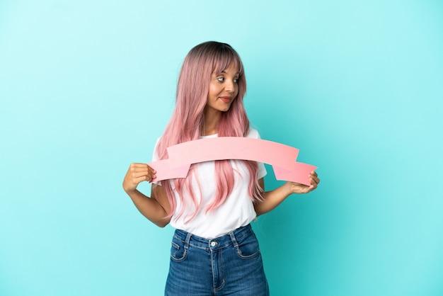 Junge gemischtrassige frau mit rosa haaren isoliert auf blauem hintergrund, die ein leeres plakat hält und zur seite schaut