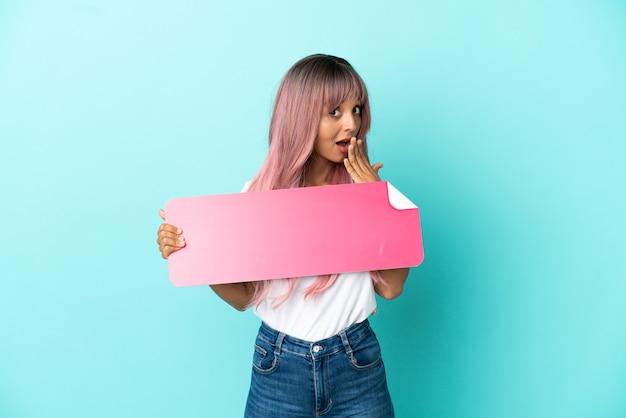 Junge gemischtrassige frau mit rosa haaren isoliert auf blauem hintergrund, die ein leeres plakat mit überraschtem ausdruck hält