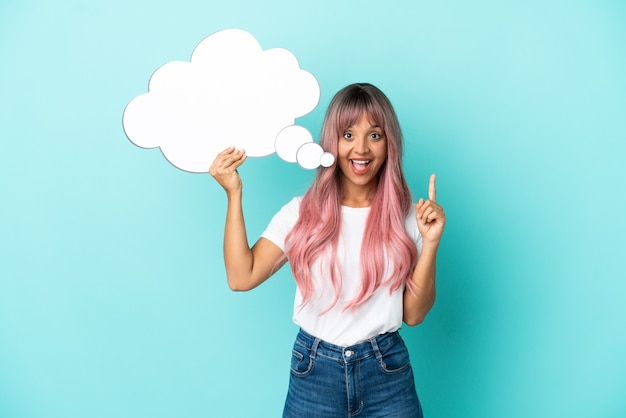 Junge gemischtrassige frau mit rosa haaren isoliert auf blauem hintergrund, die eine denkende sprechblase hält