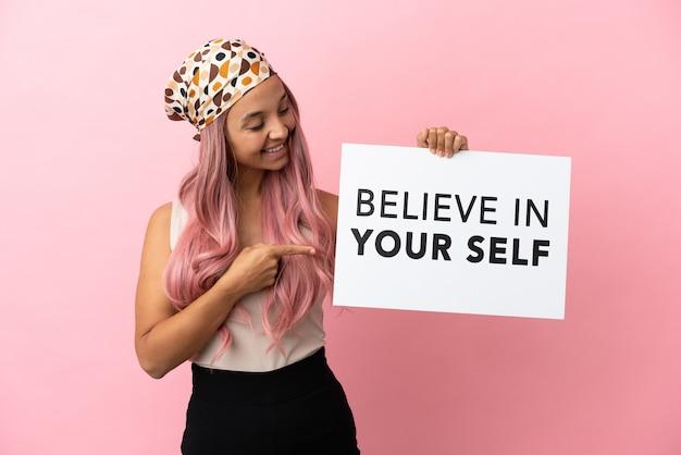 Junge gemischtrassige frau mit rosa haaren isoliert auf rosa hintergrund, die ein plakat mit dem text believe in your self hält und darauf zeigt