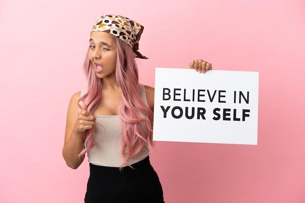 Junge gemischtrassige frau mit rosa haaren isoliert auf rosa hintergrund, die ein plakat mit dem text believe in your self hält und nach vorne zeigt
