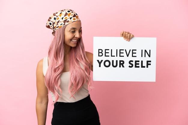 Junge gemischtrassige frau mit rosa haaren isoliert auf rosa hintergrund, die ein plakat mit dem text believe in your self hält