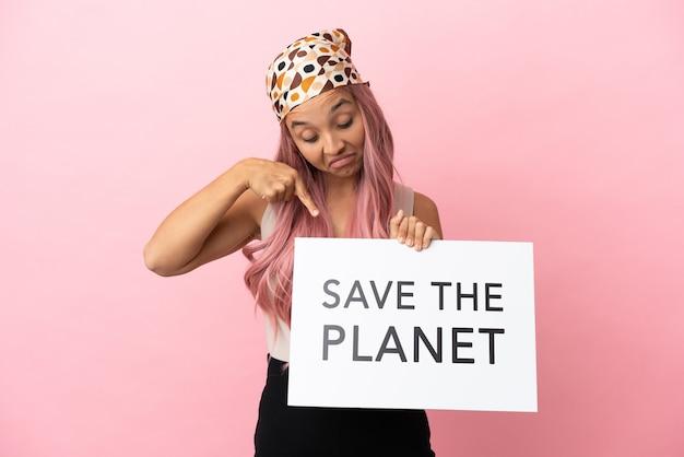 Junge gemischtrassige frau mit rosa haaren isoliert auf rosa hintergrund, die ein plakat mit dem text save the planet hält und darauf zeigt