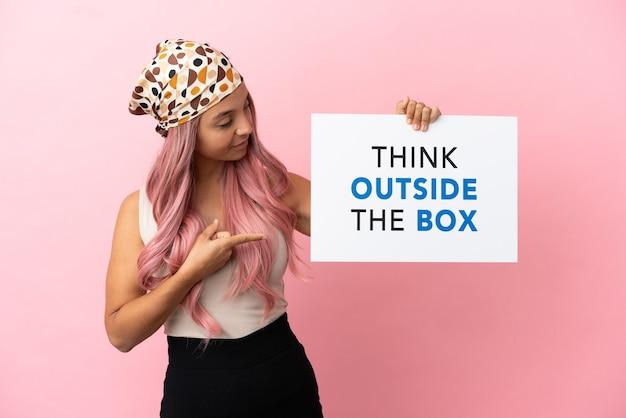 Junge gemischtrassige frau mit rosa haaren isoliert auf rosa hintergrund, die ein plakat mit dem text think outside the box hält und darauf zeigt