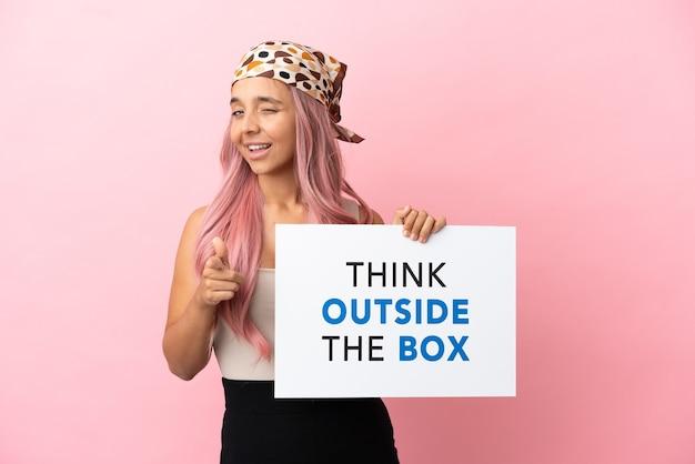 Junge gemischtrassige frau mit rosa haaren isoliert auf rosa hintergrund, die ein plakat mit dem text think outside the box hält und nach vorne zeigt