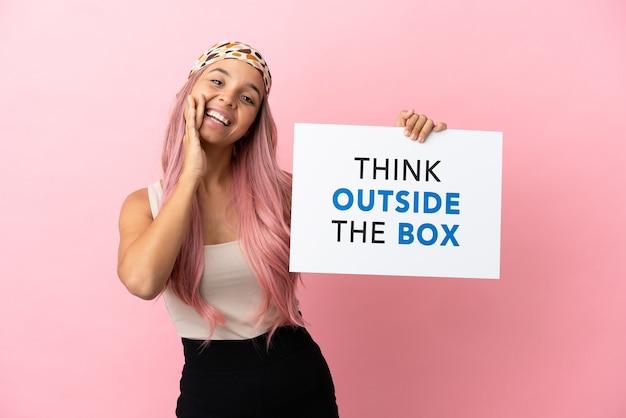 Junge gemischtrassige frau mit rosa haaren isoliert auf rosa hintergrund, die ein plakat mit dem text think outside the box hält und schreit