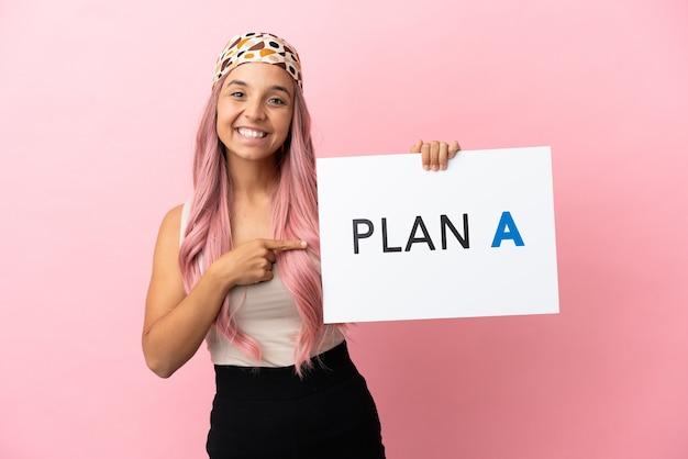 Junge gemischtrassige frau mit rosa haaren isoliert auf rosa hintergrund, die ein plakat mit der nachricht plan a hält und darauf zeigt