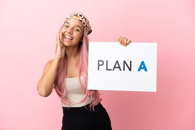 Junge gemischtrassige frau mit rosa haaren isoliert auf rosa hintergrund, die ein plakat mit der nachricht plan a hält und schreit