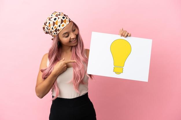 Junge gemischtrassige frau mit rosa haaren isoliert auf rosa hintergrund, die ein plakat mit glühbirnensymbol hält und darauf zeigt