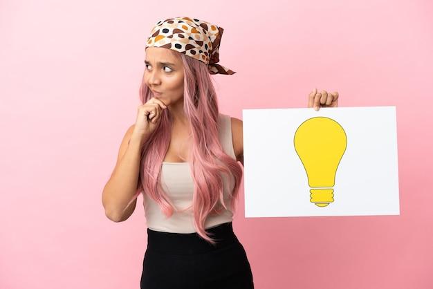 Junge gemischtrassige frau mit rosa haaren isoliert auf rosa hintergrund, die ein plakat mit glühbirnensymbol hält und denkt