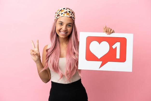 Junge gemischtrassige frau mit rosa haaren isoliert auf rosa hintergrund, die ein plakat mit like-symbol hält und einen sieg feiert