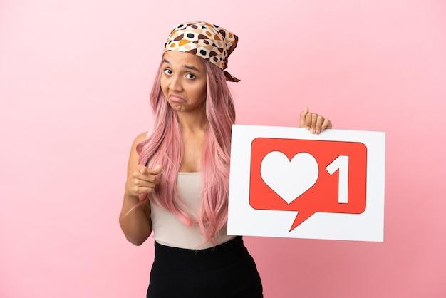Junge gemischtrassige frau mit rosa haaren isoliert auf rosa hintergrund, die ein plakat mit like-symbol hält und nach vorne zeigt