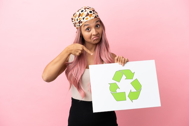 Junge gemischtrassige frau mit rosa haaren isoliert auf rosa hintergrund, die ein plakat mit recycling-symbol hält und darauf zeigt