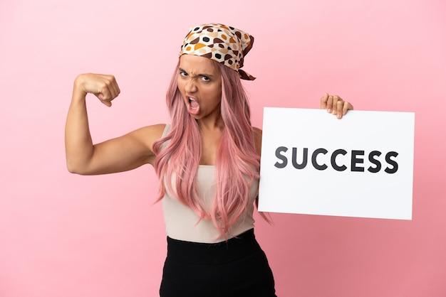 Junge gemischtrassige frau mit rosa haaren isoliert auf rosa hintergrund, die ein plakat mit text erfolg hält und starke geste macht