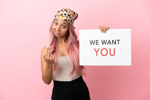 Junge gemischtrassige frau mit rosa haaren isoliert auf rosa hintergrund, die we want you board hält und kommende geste macht