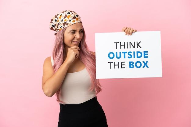 Junge gemischtrassige frau mit rosa haaren isoliert auf rosa hintergrund mit einem plakat mit text think outside the box und thinking