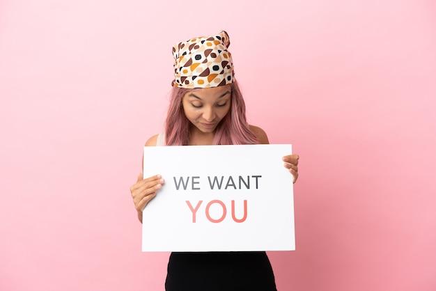 Junge gemischtrassige frau mit rosa haaren isoliert auf rosa hintergrund mit we want you board