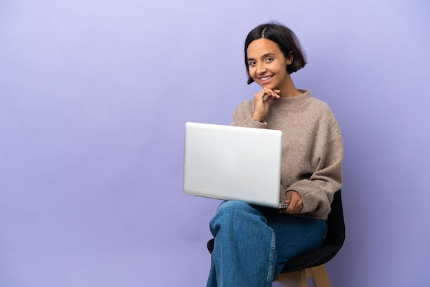 Junge gemischtrassige frau sitzt auf einem stuhl mit laptop isoliert auf lila hintergrund lachen