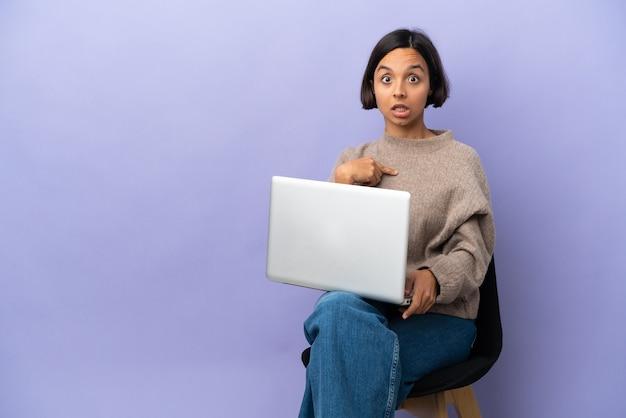 Junge gemischtrassige frau sitzt auf einem stuhl mit laptop isoliert auf lila hintergrund und zeigt auf sich selbst