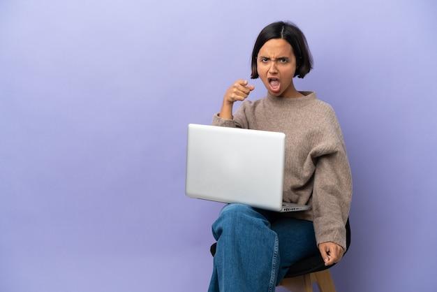 Junge gemischtrassige frau sitzt auf einem stuhl mit laptop isoliert auf violettem hintergrund, frustriert und zeigt nach vorne
