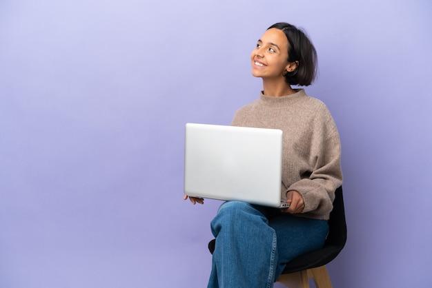 Junge gemischtrassige frau sitzt auf einem stuhl mit laptop isoliert auf violettem hintergrund und denkt eine idee, während sie nach oben schaut