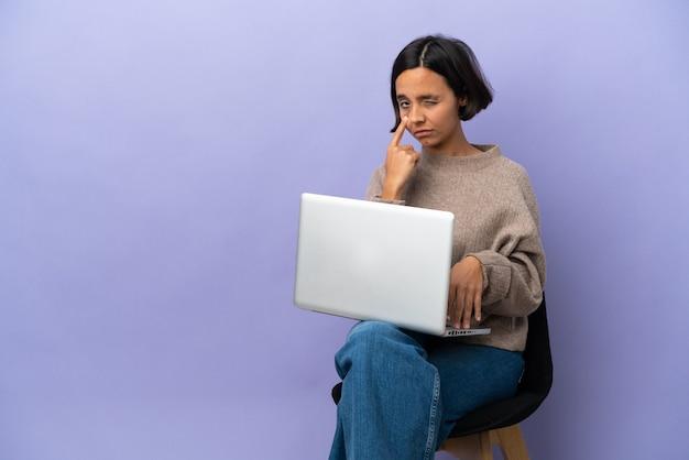 Junge gemischtrassige frau sitzt auf einem stuhl mit laptop isoliert auf violettem hintergrund und zeigt etwas